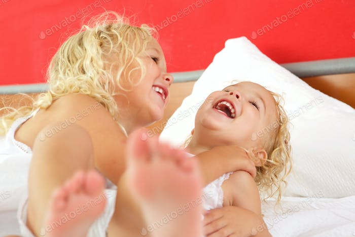 Two cute little girls playing together on bed