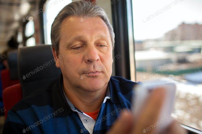 Man using mobile phone during train ride