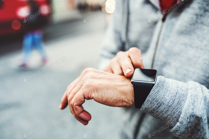 A close-up of unrecognizable man standing outdoors in city, using smartwatch.