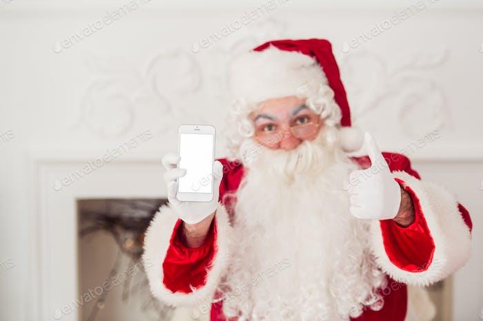 Weihnachtsmann zeigt ein Smartphone auf weißem Hintergrund