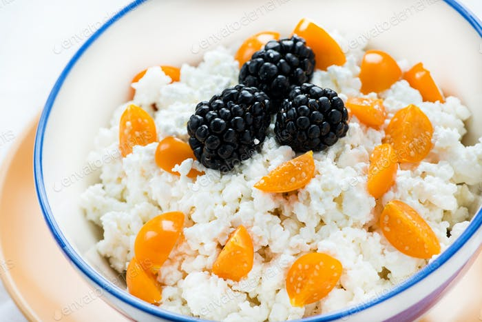 Bowl of cottage cheese with berries on light background