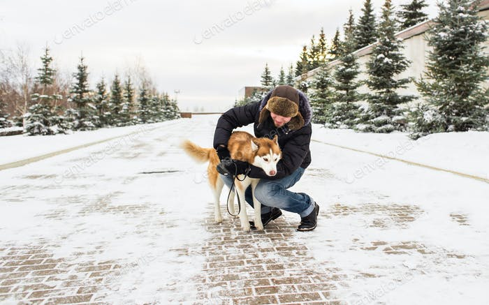 Guy with dog winter outdoors fun.
