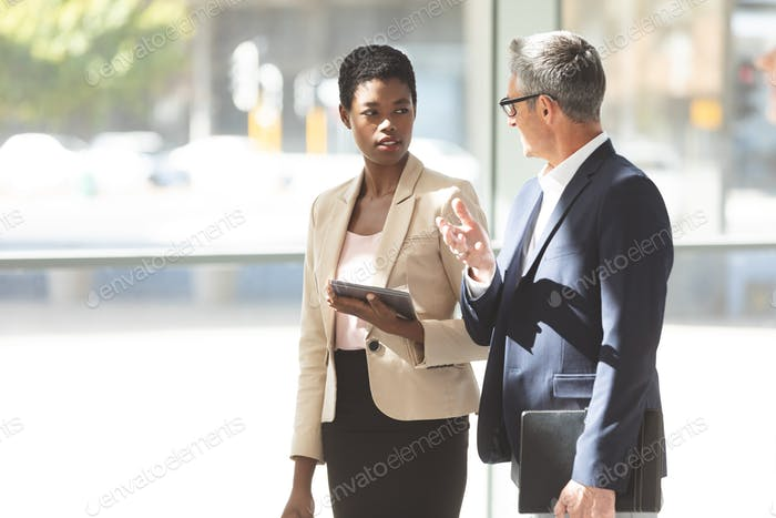 Businesswoman and Caucasian businessman interacting with each other in lobby at office lobby