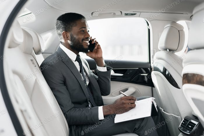 Cheerful African Businessman Chatting On Phone Working Sitting In Car