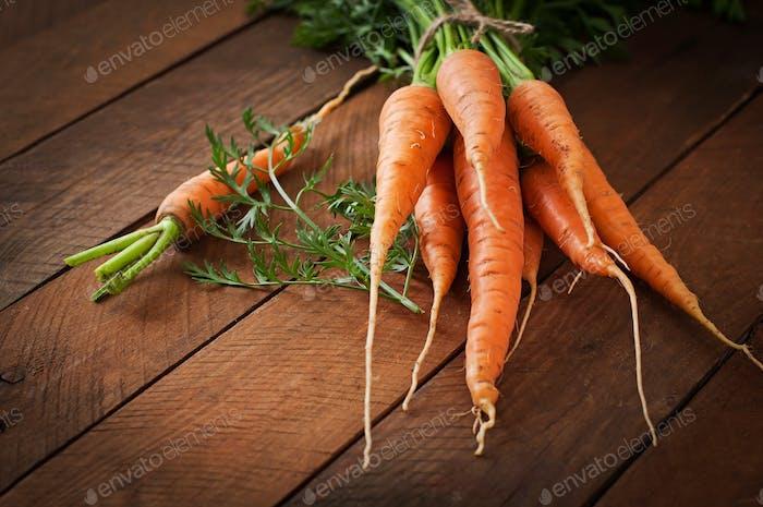 Bündel frische Karotten mit grünen Blättern über Holzhintergrund
