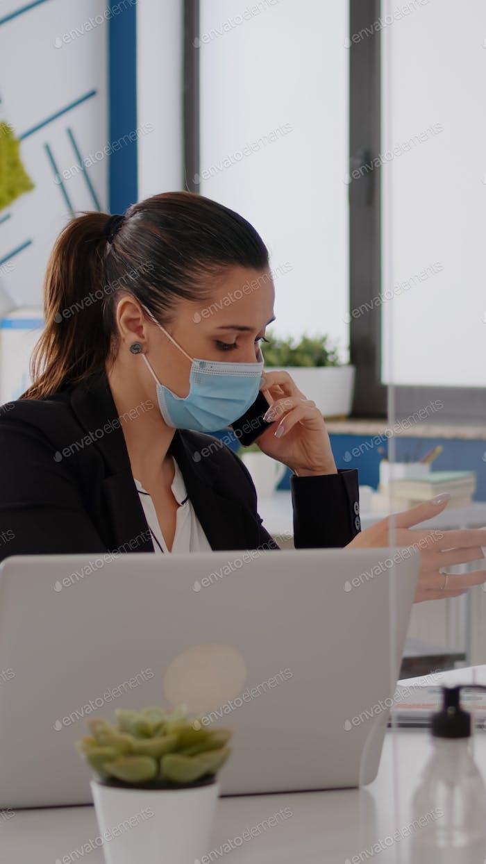 Mujer con mascarilla protectora que trabaja en la computadora portátil en la oficina de la empresa