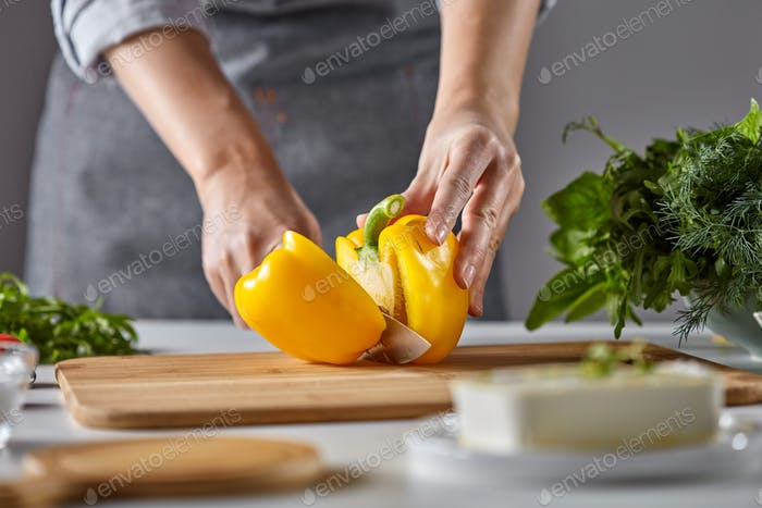 Woman's hands cut yellow pepper on a wooden board on the kitchen table. Cooking salad