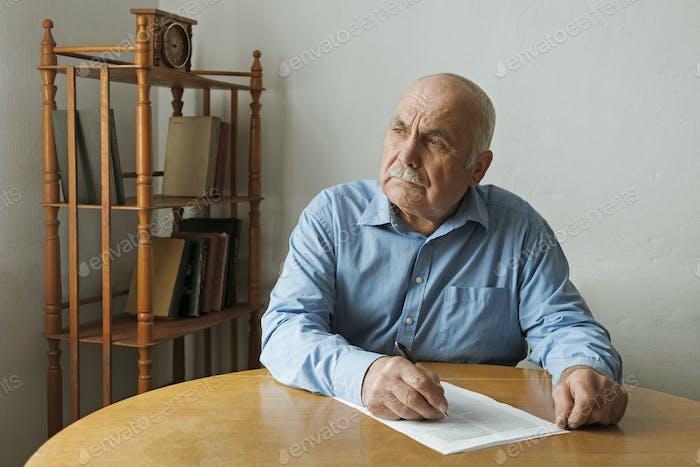 Alter Mann schreibt Notizen oder entscheidet sich zu unterschreiben