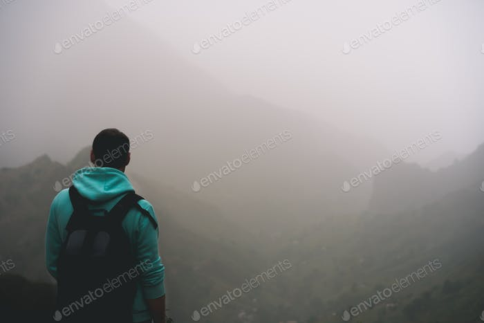 Traveler in hoodie in front of rural landscape with mountains and the ravine of Paul Valley. Santo