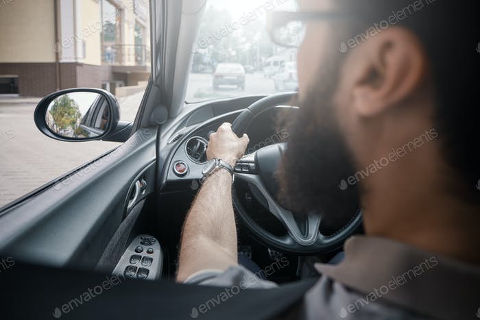 Man looking in the side mirror while driving