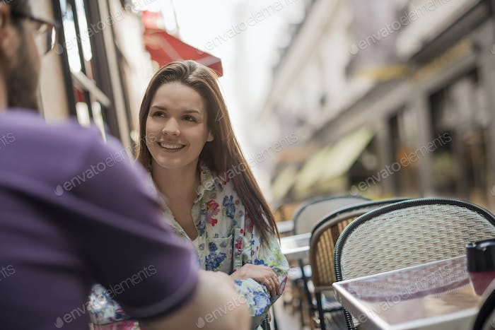 A couple seated at a table on the pavement at a cafe.