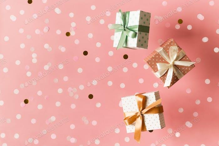 Polka dot pattern gift box with ribbon falling on pink background, levitation