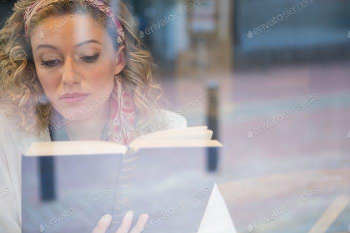 Schöne Frau Lesbuch durch Café-Fenster gesehen