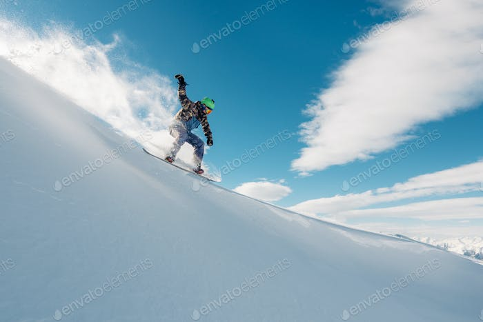 snowboarder is riding from mountain