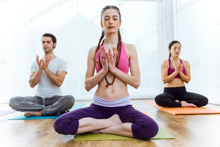 Group of people practicing yoga at home in the lotus position.
