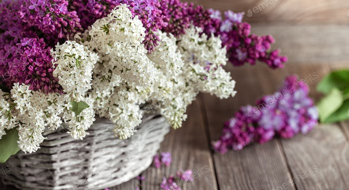 Spring composition lilac flowers in a basket on a wooden background.