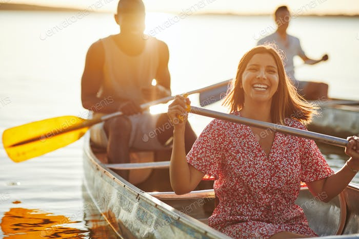 Laughing young woman canoeing with friends in the summer