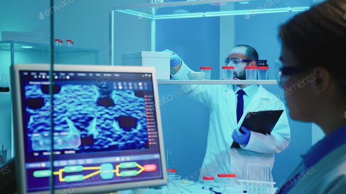 Chemist checking chemistry tools working late for medical researching