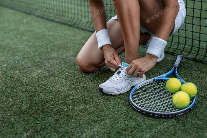 Sportswoman tying the lace close-up