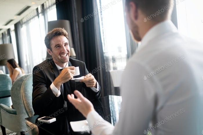 Coffee break. Two cheerful business men talking in a restaurant
