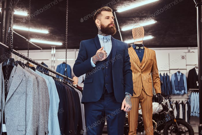 Elegantly dressed bearded shop assistant with standing near mannequin in menswear store.