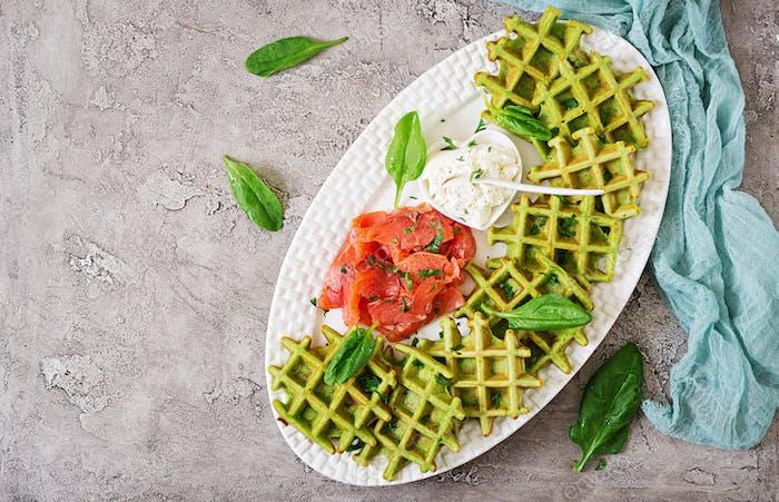 Herzhafte Waffeln mit Spinat und Frischkäse, Lachs in weißem Teller. Leckeres Essen. Draufsicht. Flache Lag