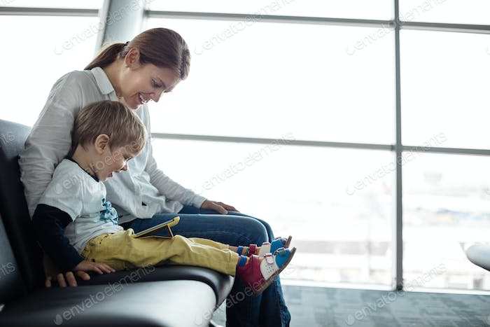 Little boy and his mother sitting in an airport departure hall and playing on a tablet