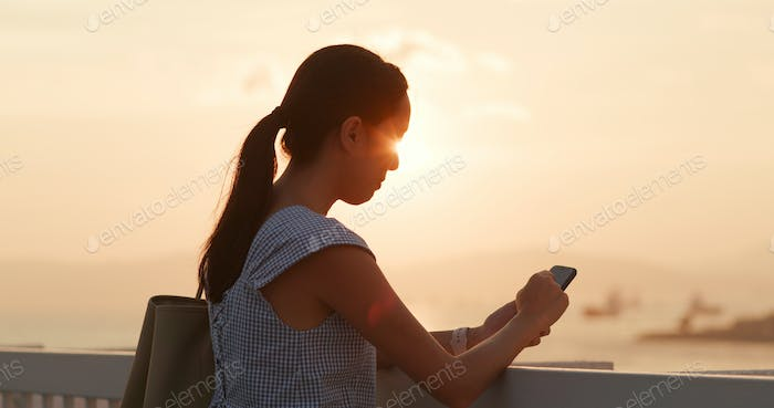 Woman use of mobile phone under sunset