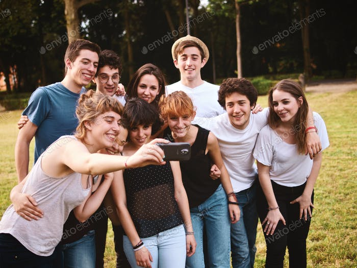 large group of teenage friends taking a selfie with a mobile camera phone