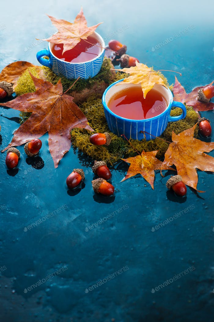 Autumn drink photography with hot tea in a blue ceramic cup, acorns in a wooden scoop and fallen