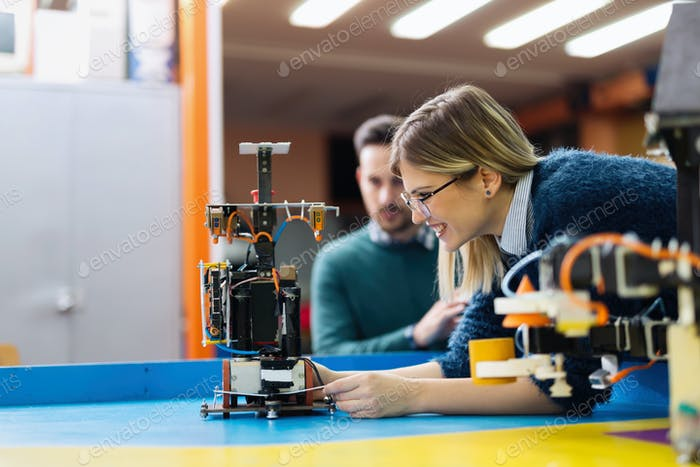 Young engineer testing her robot in workshop