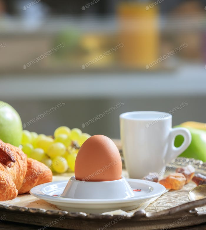 Breakfastserved, Fresh fruits, croissants, egg in eggcup and coffee on old silver tray.