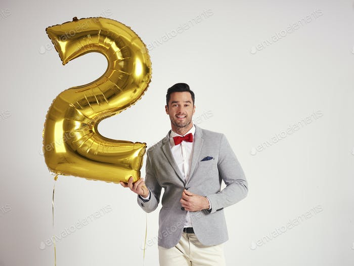 Young man with golden balloon celebrating second birthday his company