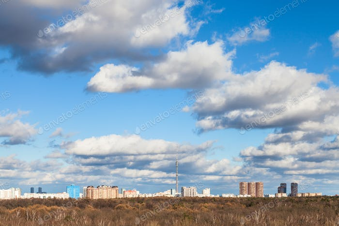 white clouds in blue sky over woods in spring day