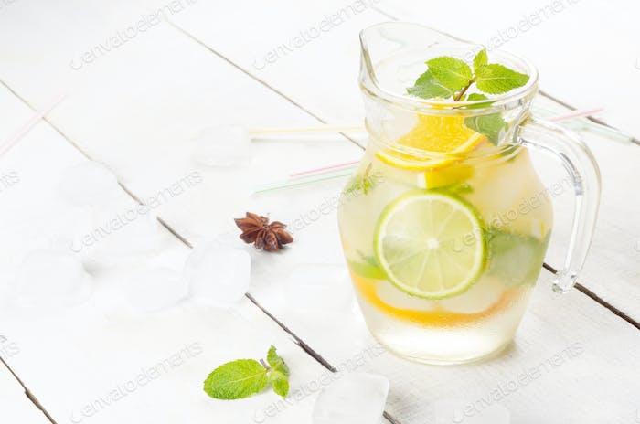 Kanne mit Limette und Orangenfruchtwasser mit Eis