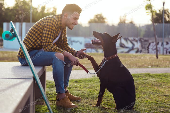 Handsome young man playing with his dog in the park.