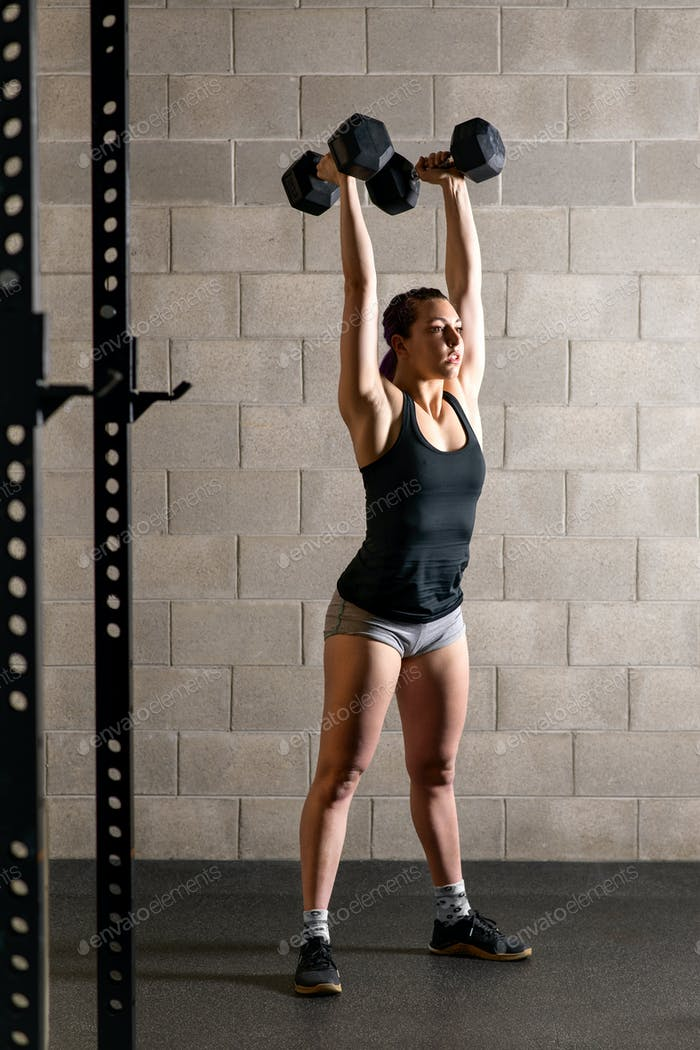 Fit strong woman doing weightlifting exercises
