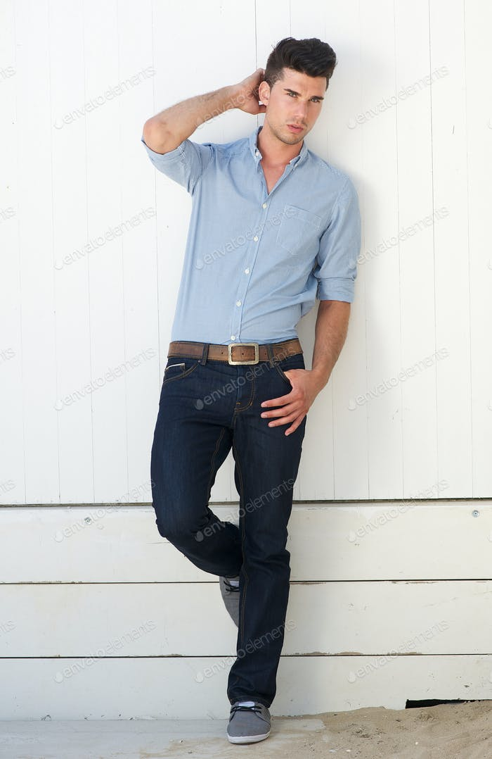 Handsome male fashion model standing against white wall outdoors