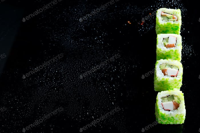 sushi roll with green caviar on black glass background . Sushi menu. Japanese food copy space