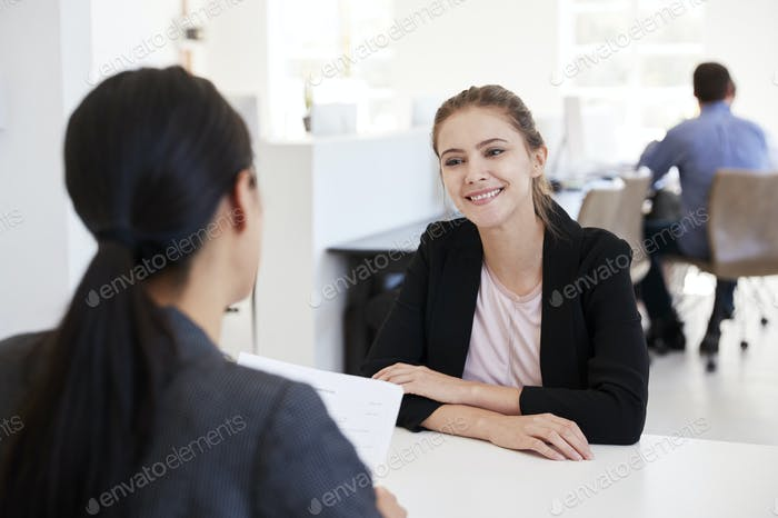 Two women sitting at an interview in an open plan office