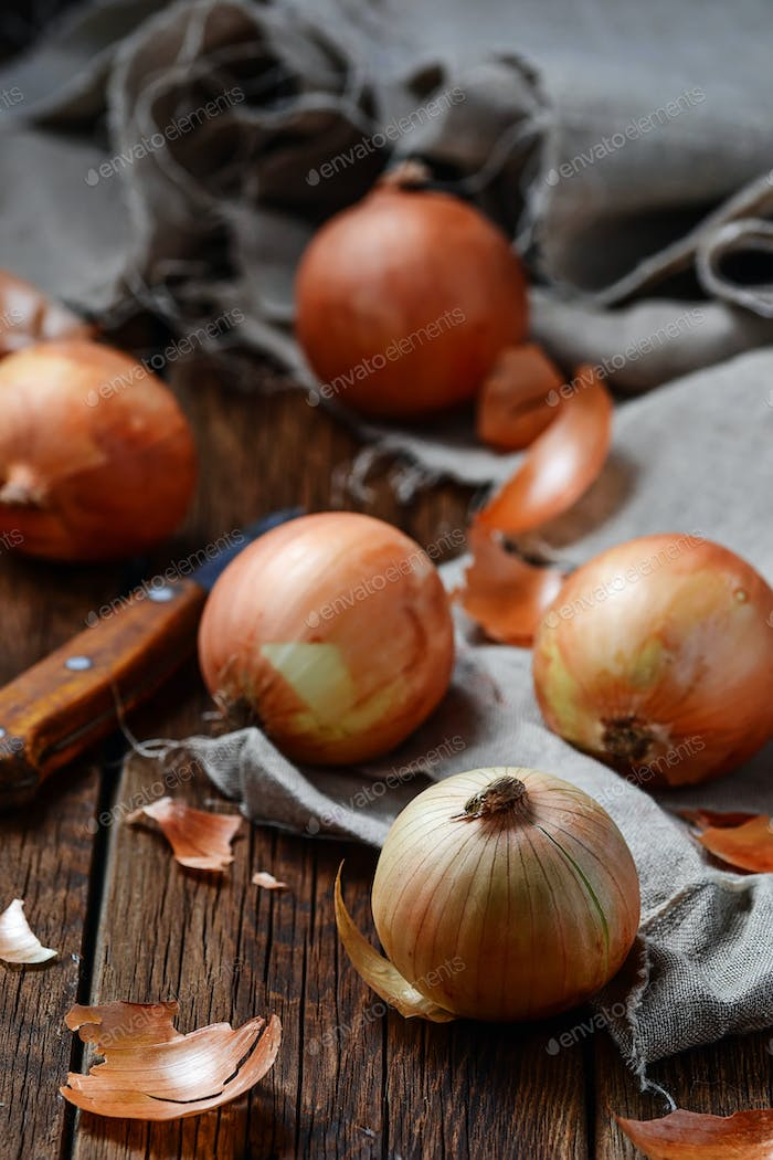 Raw onions on wooden background