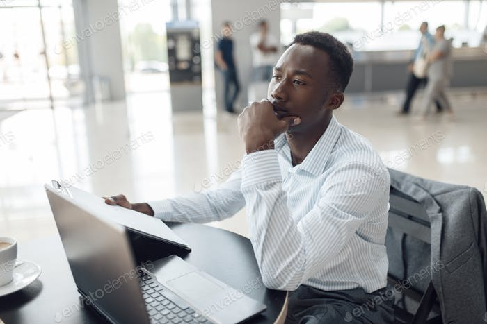 Black businessman at laptop in car dealership