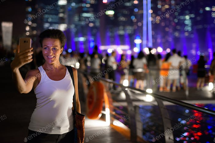 Happy mature beautiful tourist woman taking selfie in the city at night