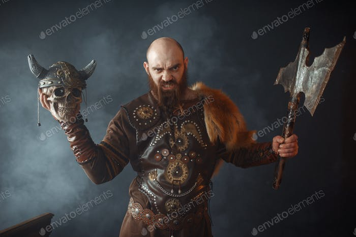 Angry viking holds enemy's skull in helmet and axe