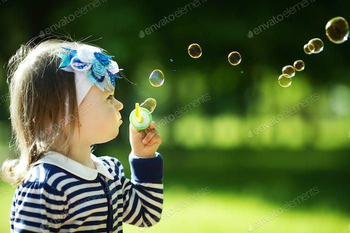 kleine lustige Mädchen spielt mit Blasen