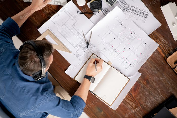 Top view of professional engineer with notebook and pencil making working notes