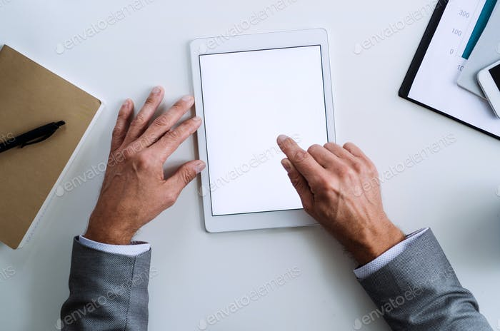 A midsection of businessman sitting at the table, using tablet. A top view. Copy space.