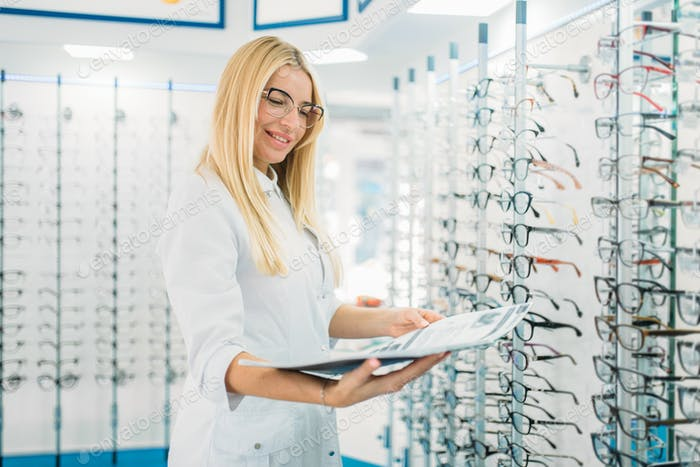 Female optician with glasses catalog in hands