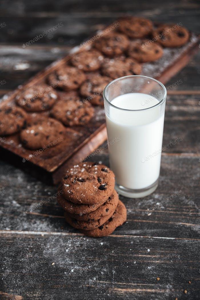 Cookies on desk on dark wooden table with milk