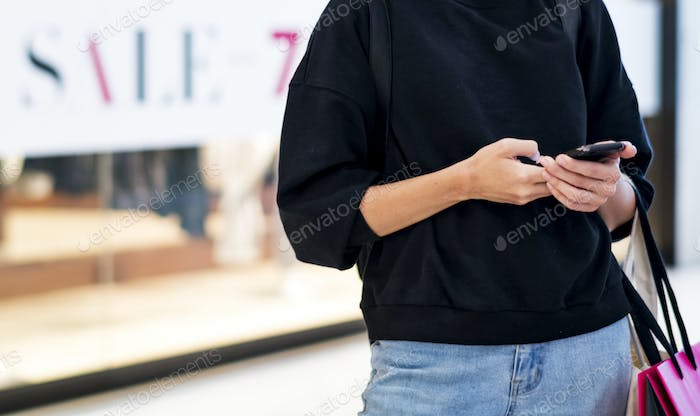 Woman playing on her phone at a shoppingmall